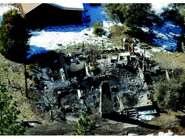 In this aerial photo, law enforcement authorities investigate the charred remains of Dorner's cabin Wednesday.