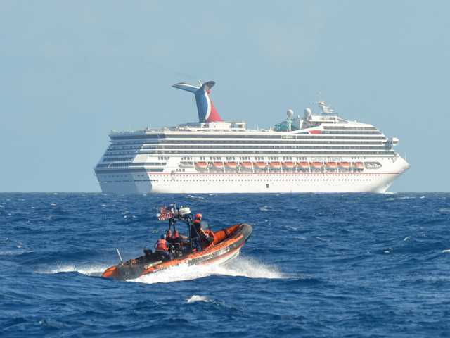 A small boat belonging to the Coast Guard Cutter Vigorous patrols near the cruise ship Carnival Triumph.