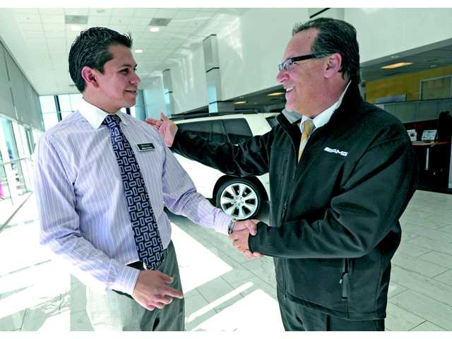 Owner and general manager Mike Sage, right, congratulates sales representative Milton Garcia on being the top performer in 2012 as they meet at Mercedes-Benz of Valencia.