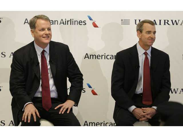 U.S. Airways CEO Doug Parker, left, and American Airlines CEO Tom Horton listen to a question during a news conference.