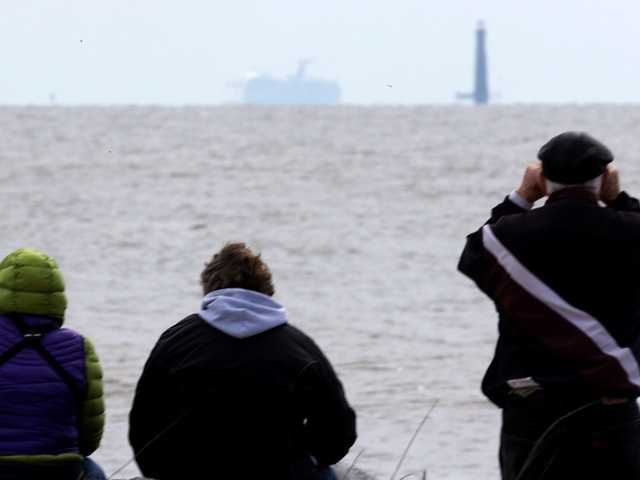 Residents sit on the shore and watch as the cruise ship Carnival Triumph is visible near Dauphin Island, Alabama on Thursday. A tow line snapped, setting the vessel adrift once again.
