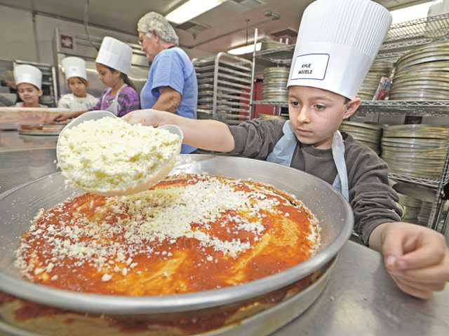 Ernesto Pineda adds toppings to his pizza as he and his fourth-grade classmates prepare food.