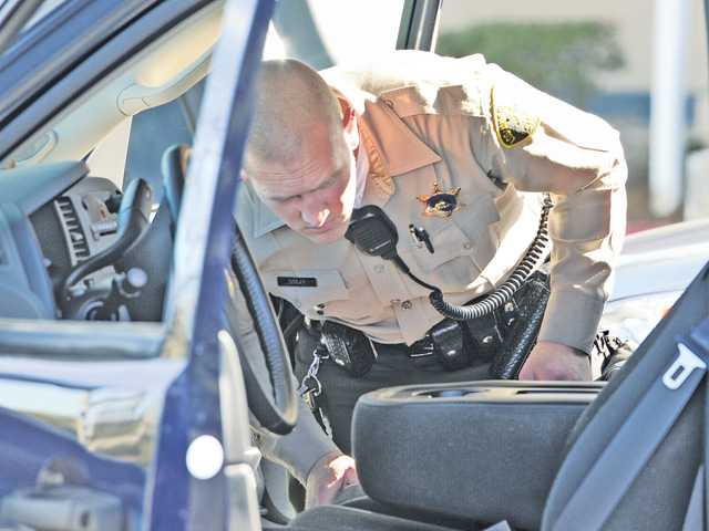 The Chevolet pickup truck that was driven by a 17-year-old is searched by a sheriff's deputy at the Target parking lot on Magic Mountain Parkway in Valencia on Friday. The minor was arrested for allegedly brandishing a knife during a road rage incident. Signal photo by Dan Watson
