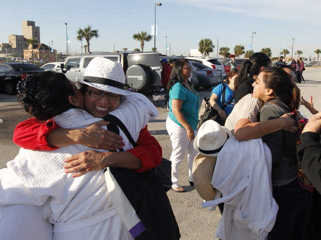 Patricia Wagner, right, hugs her sister Mercedes Perez de Colon,as their group is reunited after taking separate buses from Mobile, Ala., where the disabled Carnival ship Triumph docked. (AP)