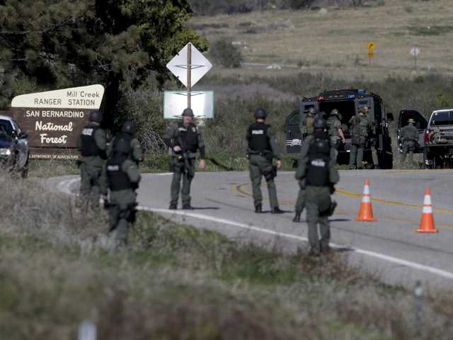 Law Enforcement personnel gear up along Hwy 38 during the hunt for accused killer and fired Los Angeles police officer, Christopher Dorner in Yacaipa, Tuesday. (AP)