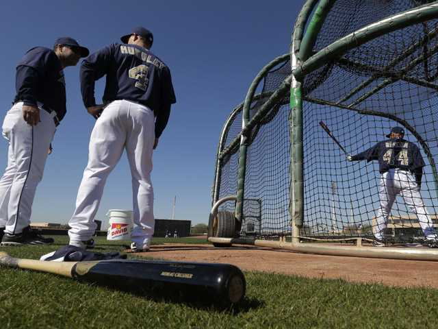 San Diego Padres hitting coach Phil Plantier, left, and catcher Nick Hundley (4) talk while catcher Rene Rivera bats during a spring training baseball workout. (AP)