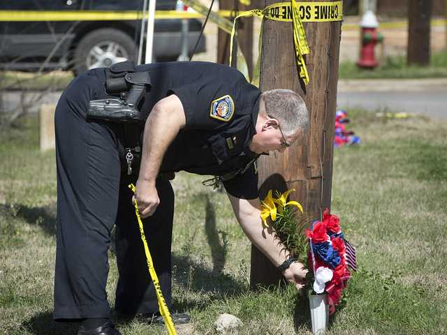 Bryan Police Officer Al Wescoat straightens flowers at a makeshift memorial near a Knights of Columbus Hall. (AP)