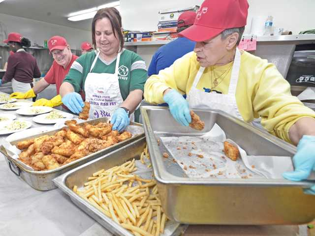 Volunteers from left, Paul Travers, Sondra Tersigni, and Diane Sorensen prepare fried fish and french fries for some of the hundreds of dinners served at the Lenten Fish Fry held at St. Clare's Catholic Church in Canyon Country on Friday evening.