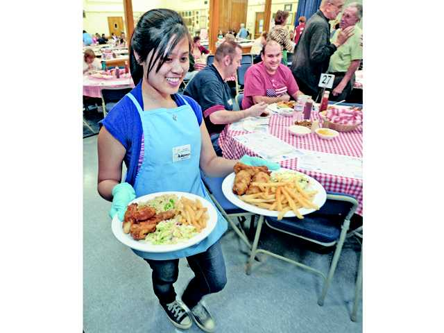 Adeann Orlino serves two of the hundreds of fish dinners that are served at the Lenten Fish Fry held at St. Clare's Catholic Church in Canyon Country on Friday evening. The St. Clare's Lenten Fish Fries will continue to run 4:30-8 p.m. Fridays through March 22.