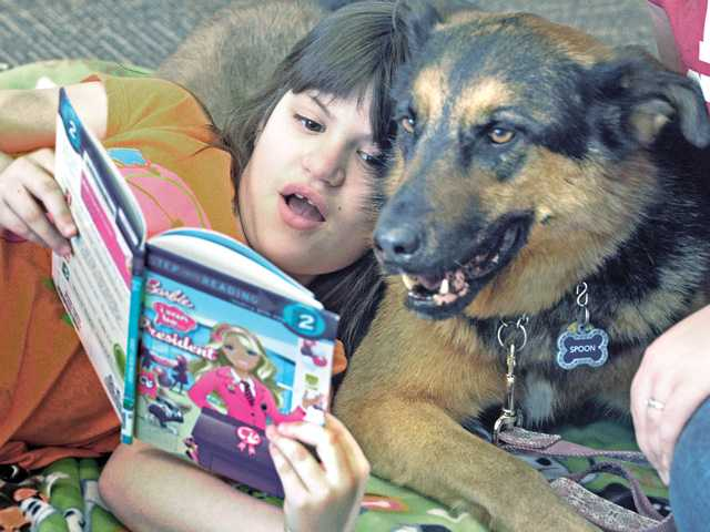 Samantha Gorenson, 7, reads aloud from her Barbie book to Spoon, an 8-year-old German shepherd mix at the read to dogs event held at the Newhall Library on Saturday. (Dan Watson/The Signal)