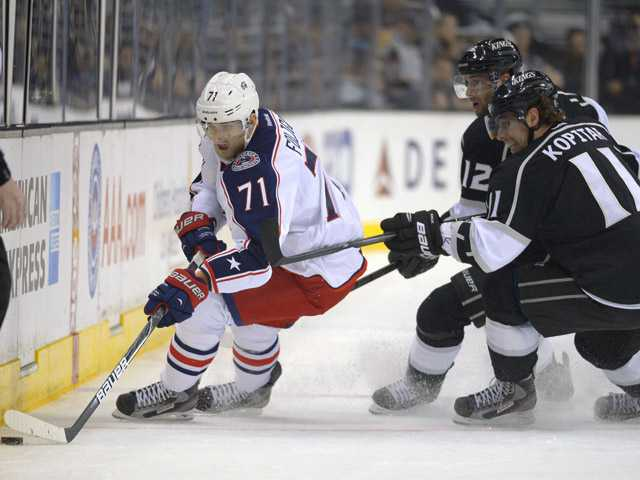 Columbus Blue Jackets left wing Nick Foligno, left, battles for the puck along with Los Angeles Kings Simon Gagne, center, and Anze Kopitar on Friday in Los Angeles.