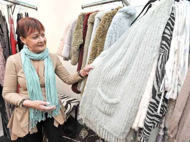 Margo Hudson looks through items on a rack as she prepares to open The Closet on Main in Newhall.