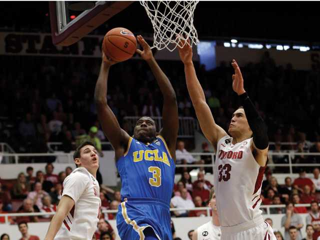 UCLA 's Jordan Adams (3) drives to the basket between Stanford 's Dwight Powell (33) and Rosco Allen, left, during the first half of an NCAA college basketball game in Stanford Saturday.
