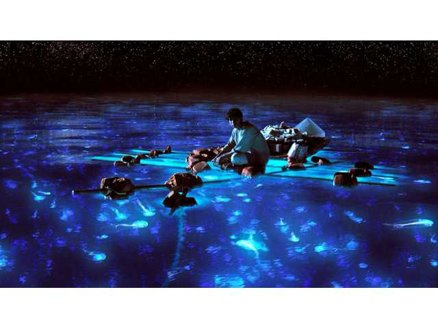 "Suraj Sharma as Pi Patel taking in the bioluminescent wonders of the sea in a scene from the film, ""Life of Pi."""