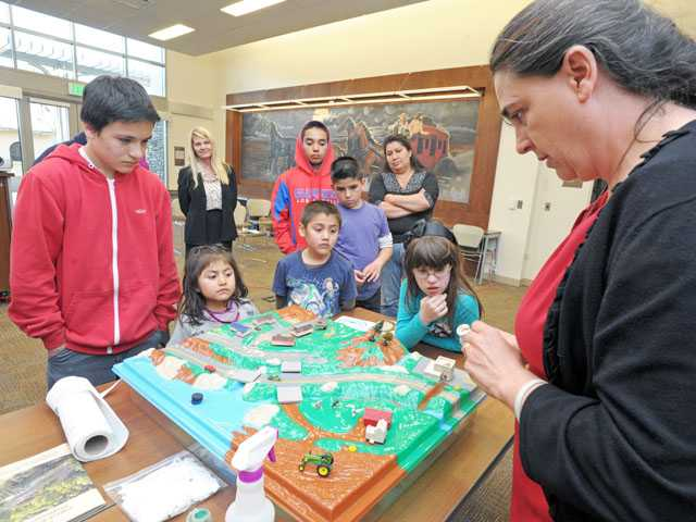 Sustainability planner Heather Merenda shows the effect of pollution in stormwater which leads to the Santa Clara River on a model at the Newhall Library on Wednesday.