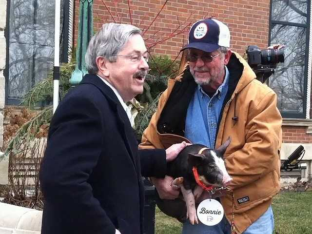Gov. Terry Branstad visits with a farmer on Feb. 8. Branstad is heading to California to recruit West Coast businesses to Iowa.