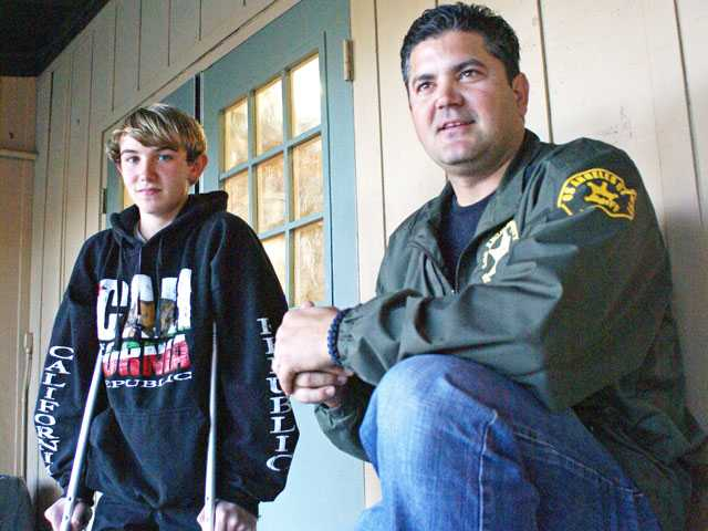 Timothy Hulin, 14, still on crutches after being hit by a car, talks about the crash with the man who kept reminding him to wear a helmet — Deputy Brian Rooney of the SCV Sheriff's Station, who heads the Youth Activity League in Val Verde. (Jim Holt/The Signal)