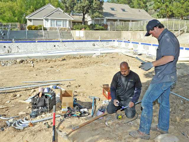 Victor Contreras, center, and Jordan Checots of Valencia Electric work Monday near an HOA pool damaged by vandals in North Valencia. (Jonathan Pobre/The Signal)