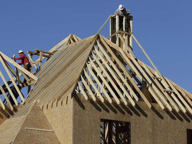 Workers install a roof on a home under construction in Charlotte, N.C.