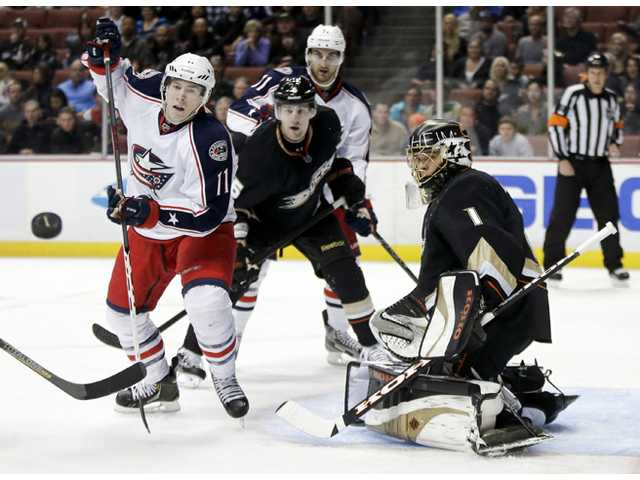 Anaheim Ducks goalie Jonas Hiller deflects a shot by Columbus Blue Jackets left wing Matt Calvert, left, on Monday in Anaheim.