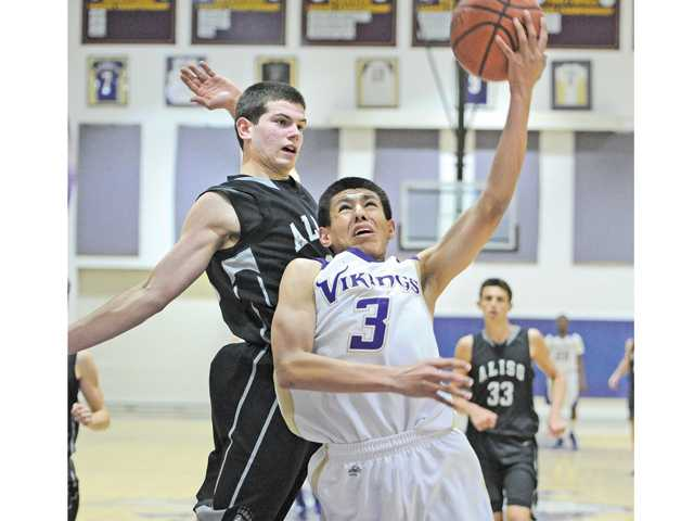 Valencia's Angel Cardenas (3) shoots against Aliso Niguel defender Scott Lynds (3) at Vaelncia High on Tuesday. Valencia lost the game 64-52.