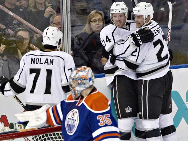 Los Angeles King Jordan Nolan (71) Colin Fraser (24) and Trevor Lewis (22) celebrate Fraser's goal against the Edmonton Oilers in Edmonton, Alberta, on Tuesday.