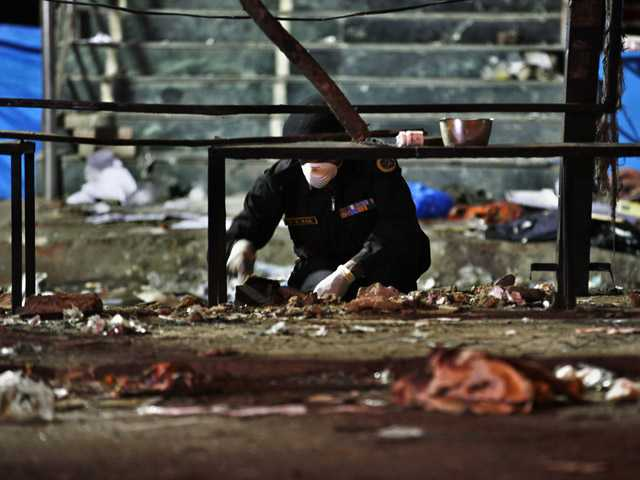 An official of India's National Investigation Agency collects evidence from the debris at one of the two bomb blast sites.