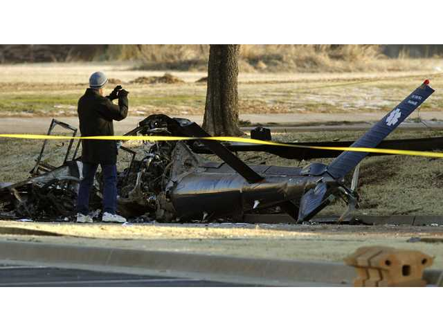 Investigators with the FAA look over the wreckage of a medical helicopter which crashed Friday.