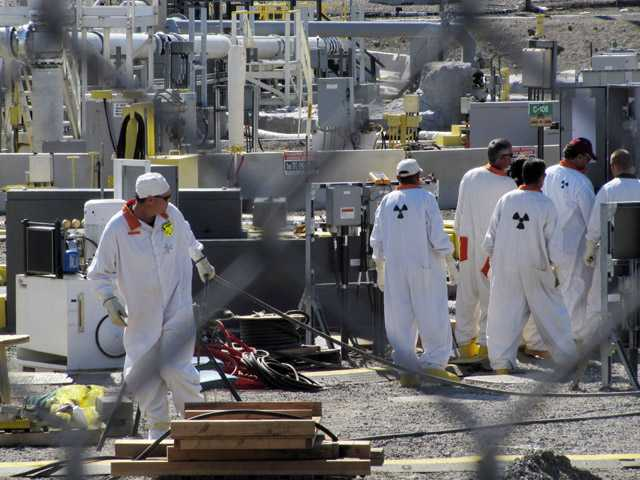 Workers at the Hanford nuclear reservation work around a a tank farm where highly radioactive waste is stored underground near Richland, Wash.