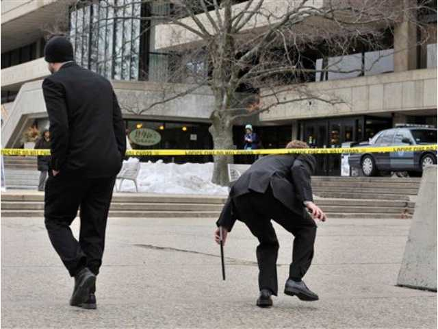 Pedestrians on the MIT Campus in Cambridge, Mass., duck underneath police tape, Saturday, Feb. 23, 2013, after police responded to reports of a gunman on campus that Cambridge police later said were unfounded. Police said that officers searched for a man reported to be carrying a long rifle and wearing body armor and found nothing.