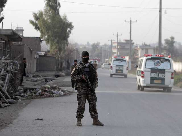 A security official stands guard at the scene of a suicide car bomb attack which killed and injured several people at the National Directorate of Security in Jalalabad, Afghanistan, Sunday.