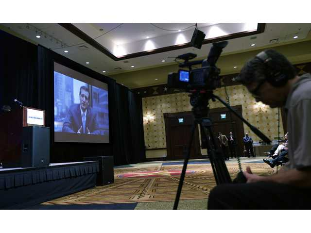 Sen. Ted Cruz, R-Texas is seen on a video screen as he addresses a conservative forum at the Texas Public Policy Foundation.