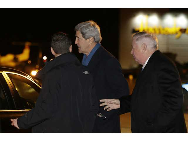 U.S. Secretary of State John Kerry, centre, is greeted by U.S. Ambassador Louis Susman upon his arrival in Britain.