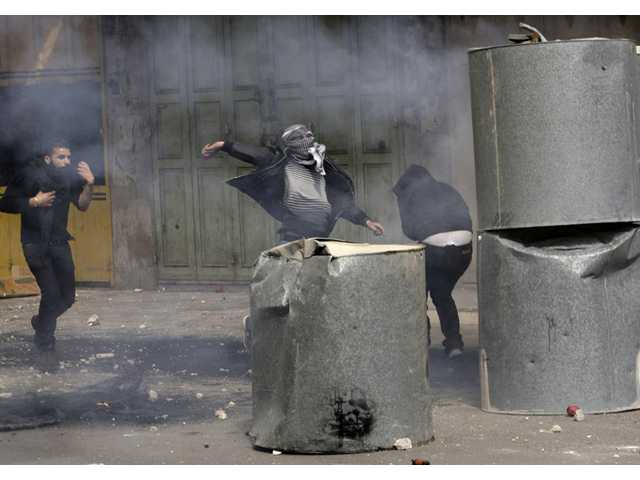 Palestinians throw stones during clashes with Israeli troops in the West Bank city of Hebron, following the death of Arafat Jaradat.