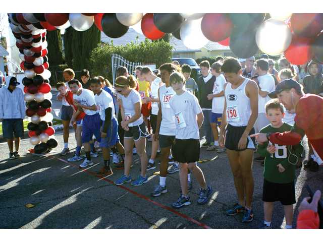 Runners set out from the starting line of the WiSH Education Foundation Run For Gold at Placerita Junior High School, running along the South Fork Trail on Sunday.