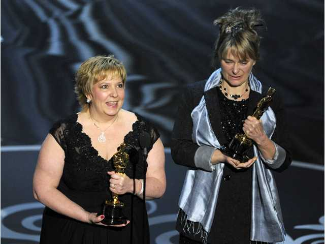 "Lisa Westcott, left, and Julie Dartnell accept the award for best makeup and hairstyling for ""Les Miserables"" during the Oscars at the Dolby Theatre."