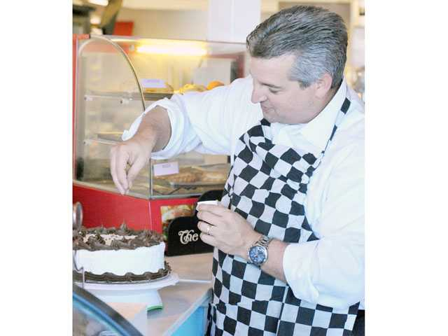 Martin Rodriguez, vice president of the board of the SCV Youth Project, tries his hand at cake decorating.