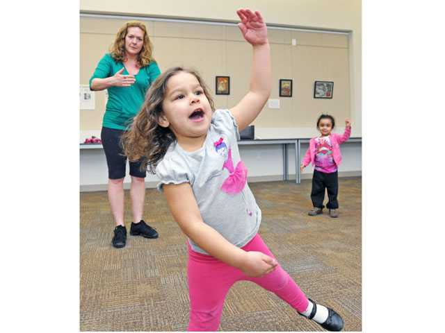 Dylan Kate Muller, center, and Jasleen Ranu, both 3, pose like robots during a dance class taught by Muller's mother Katina Childs-Muller, left, at the Old Town Newhall Library on Tuesday.