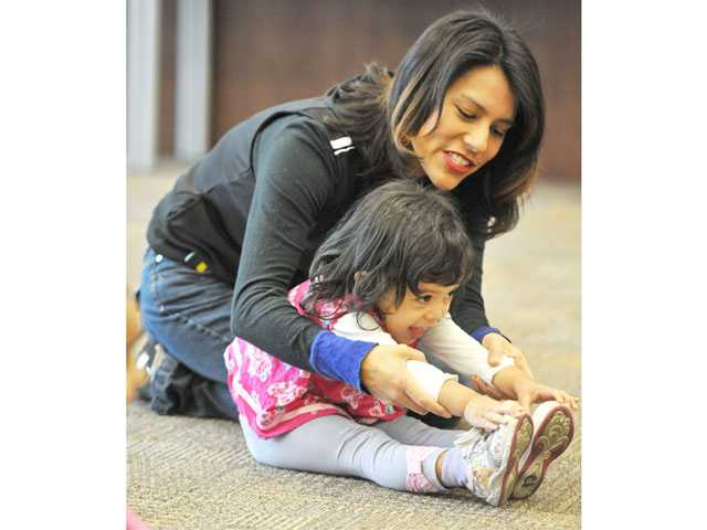 Julie Arreola helps her daughter Ava Arreola, 2, stretch during a dance class at the Old Town Newhall Library on Tuesday.