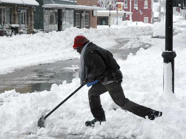 James Smith clears snow from sidewalks Tuesday in downtown Sedalia, Mo.