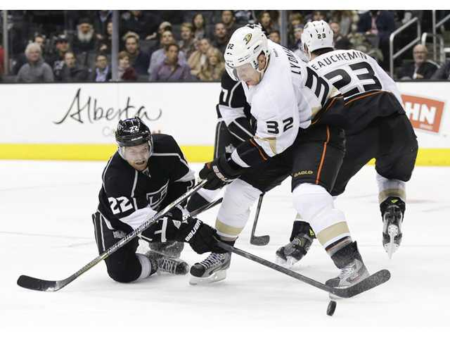 Los Angeles Kings center Trevor Lewis, left, shoots past Anaheim Ducks defenseman Toni Lydman (32) on Monday in Los Angeles.