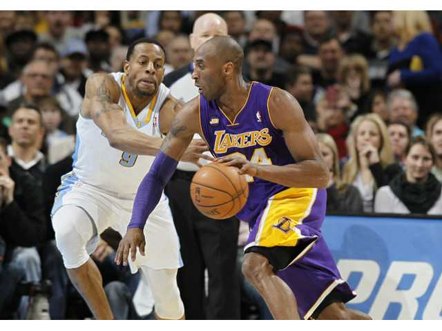 Los Angeles Lakers guard Kobe Bryant, front, works ball inside against Denver Nuggets guard Andre Iguodala on Monday in Denver.