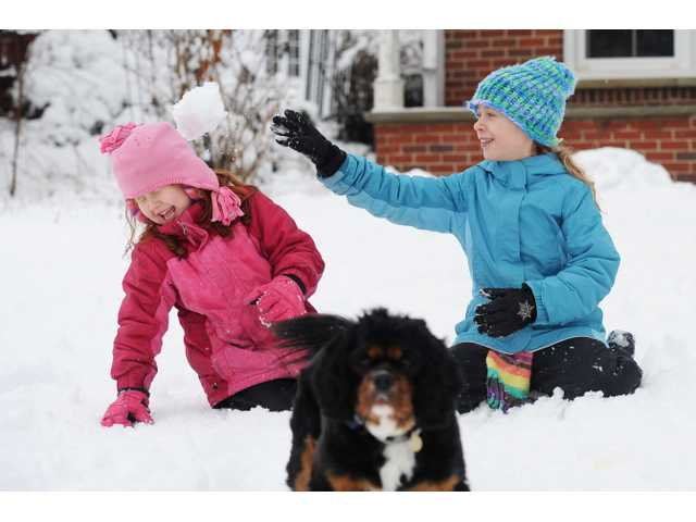 Six-year-old Jaylee Oeschger, 6, laughs as she is hit in the head with a snowball thrown by her sister Ileana, 10 in Ann Arbor, Mich.