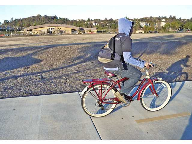 A man cycles on the bike path along Newhall Ranch Road looking toward the empty lot in front of Real Life Church near Grandview Drive. The lot will become a city park and parking lot.
