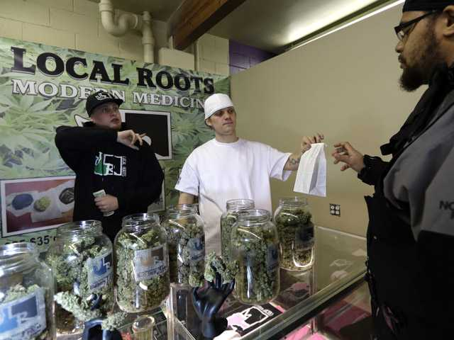 Zerin Beverly, right, purchases medical marijuana from Kyle McClanahan, left, and Matthew VanKooten during the grand opening of the Seattle location of the Northwest Cannabis Market, for sales of medical marijuana products on Wednesday.