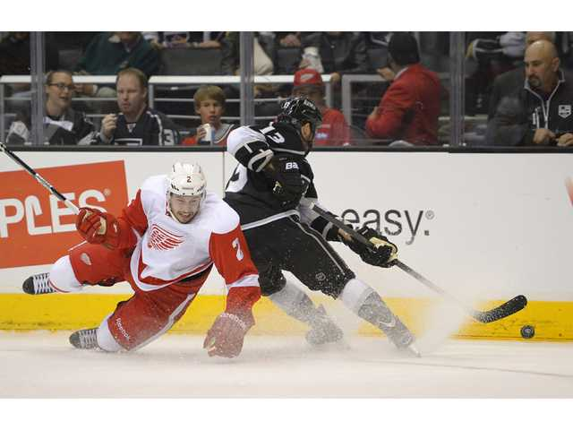 Detroit Red Wings defenseman Brendan Smith, left, falls to the ice as Los Angeles Kings left wing Kyle Clifford takes the puck.
