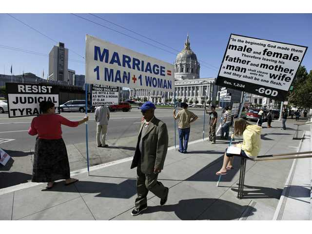 This 2011 file photo shows a man walking past a group of people protesting against gay marriage outside the California Supreme Court.