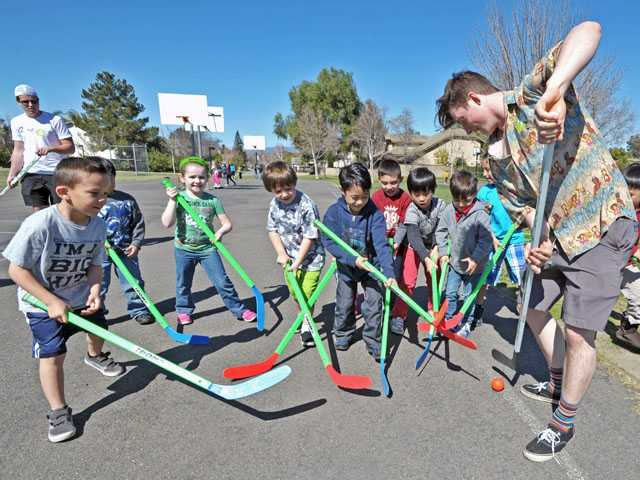 Alex Descheneaux, right, of the Valencia Flyers ice hockey team, gets into a game of hockey with kindergarteners at Valencia Valley Elementary School on Thursday. Five teammembers were on hand to introduce hockey to students.