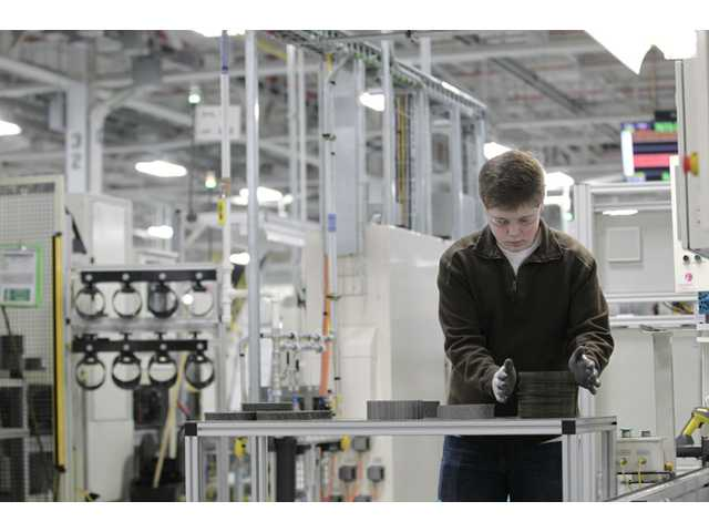 In this Thursday photo, Jordan Kenyon works on the assembly line at the Chrysler transmission plant in Kokomo, Ind.