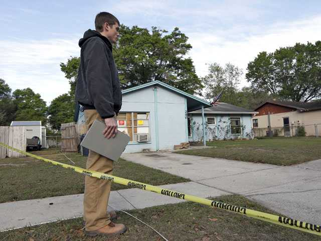 An engineer stands in front of a home where sinkhole opened up today. (AP)